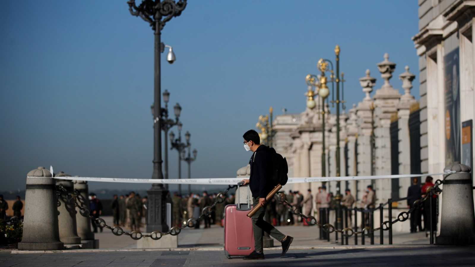 Un joven con su maleta pasa ante el Palacio Real de Madrid, este viernes.