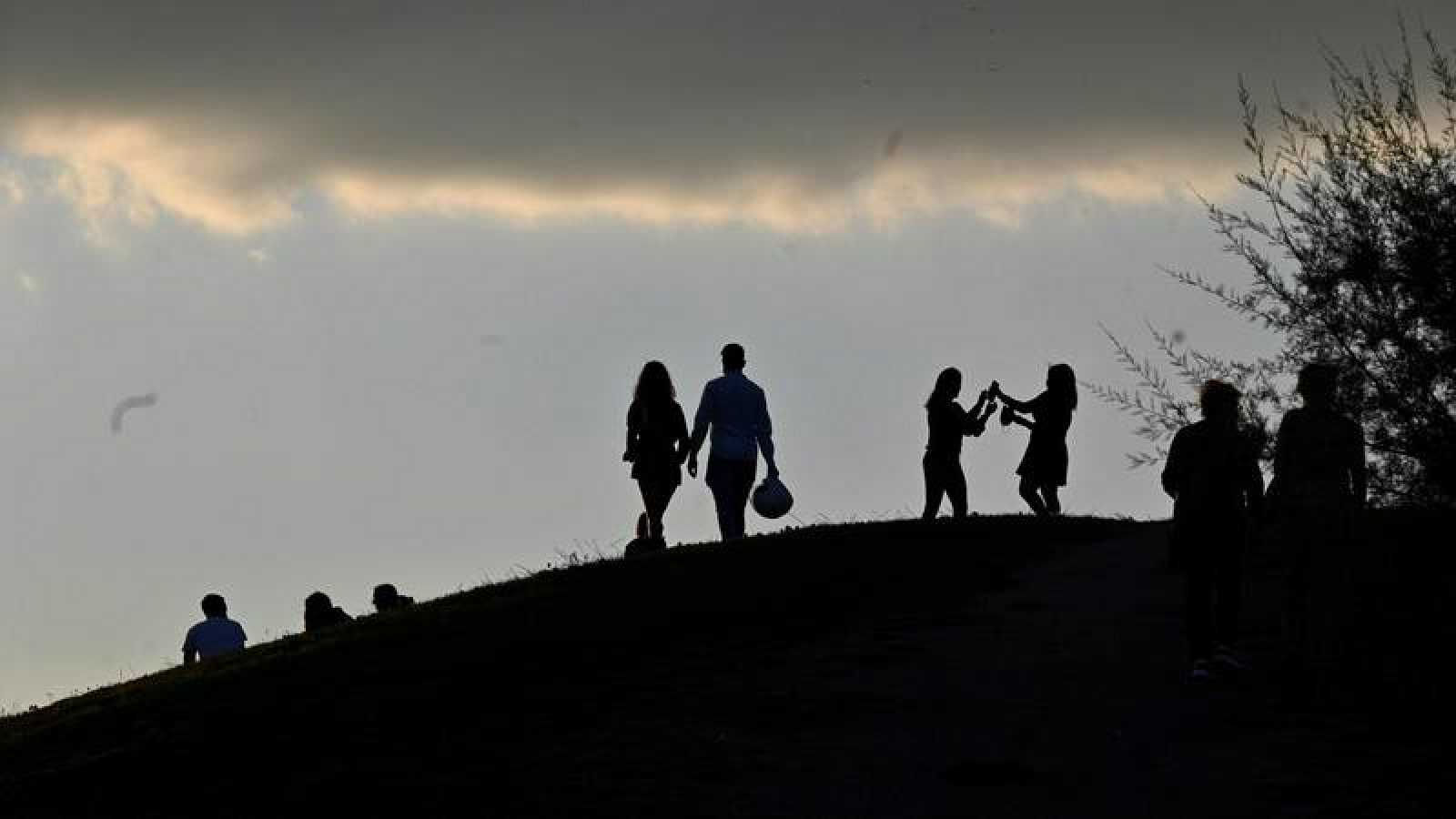 Personas viendo el atardecer desde el Parque del Cerro del Tío Pío, en el distrito de Puente de Vallecas, Madrid.