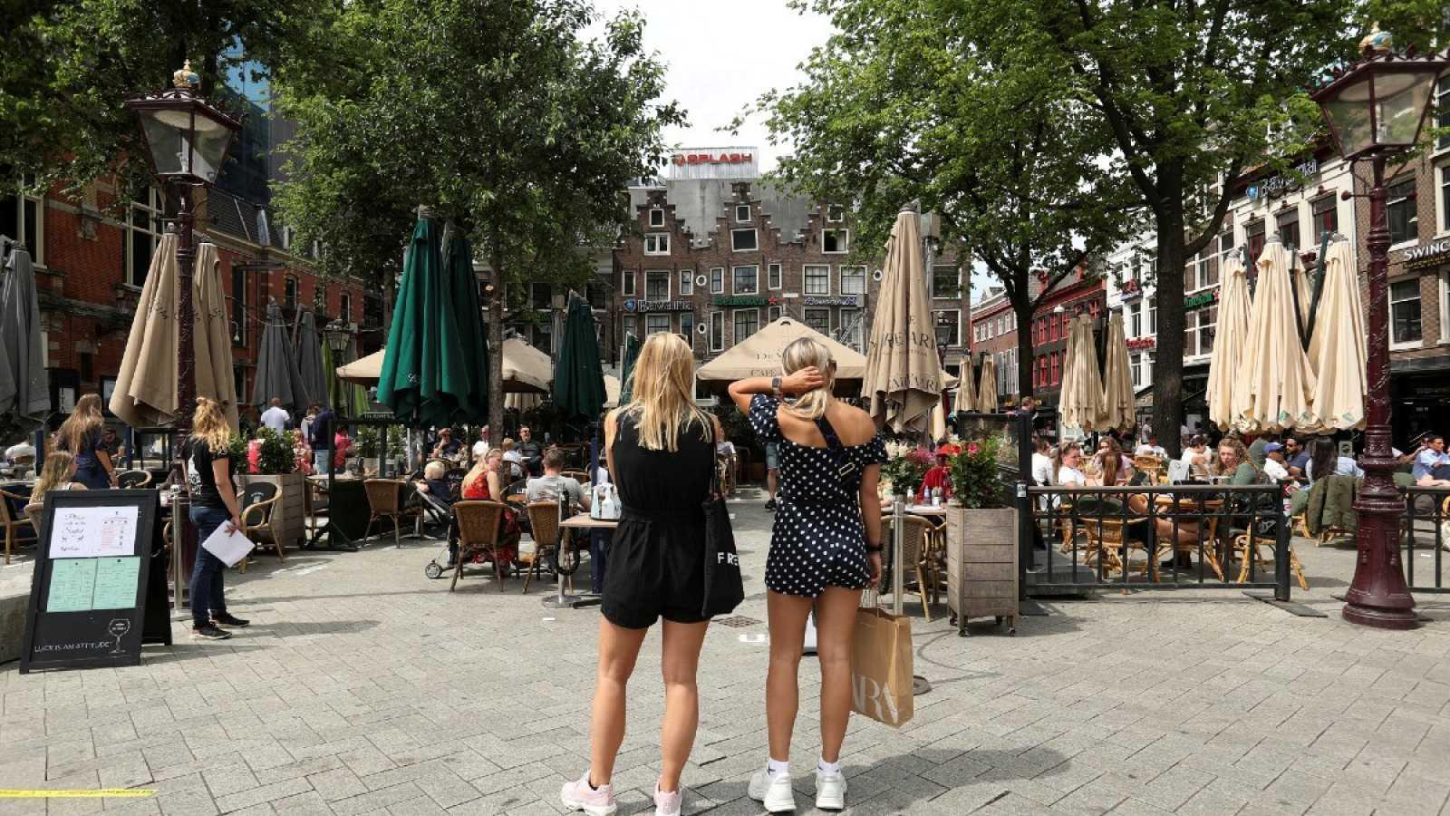 Dos mujeres esperan para sentarse en una terraza tras el alivio de las medidas por la pandemia el pasado junio, en Ámsterdam.