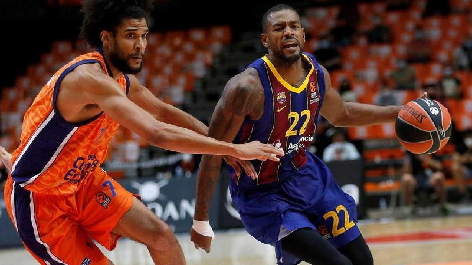 El ala-pívot francés del Valencia Basket Louis Labeyrie (i) defiende al escolta estadounidense del FC Barcelona Cory Higgins (d).