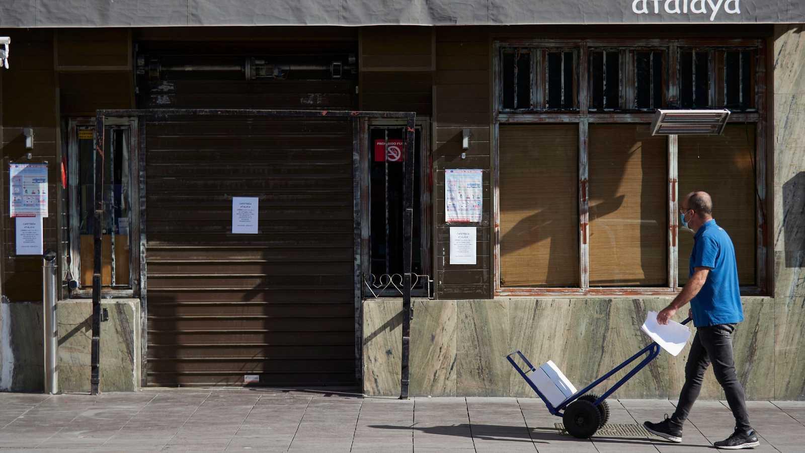 Un repartidor pasa junto a una cafertería cerrada temporalmente por el Covid-19 en Peralta (Navarra).