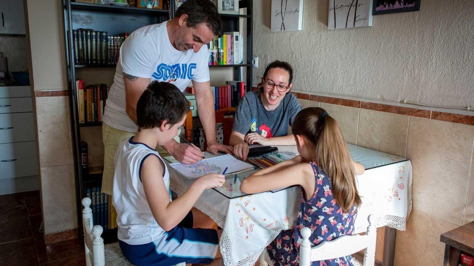 Patricia, su marido y sus dos hijos alrededor de la mesa en el cuarto de estar de su casa.