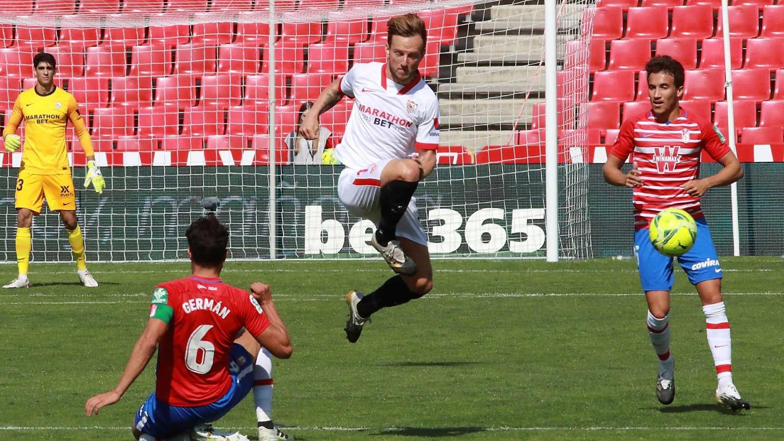 El jugador del Sevilla Rakitic despeja el disparo de Germán, del Granada