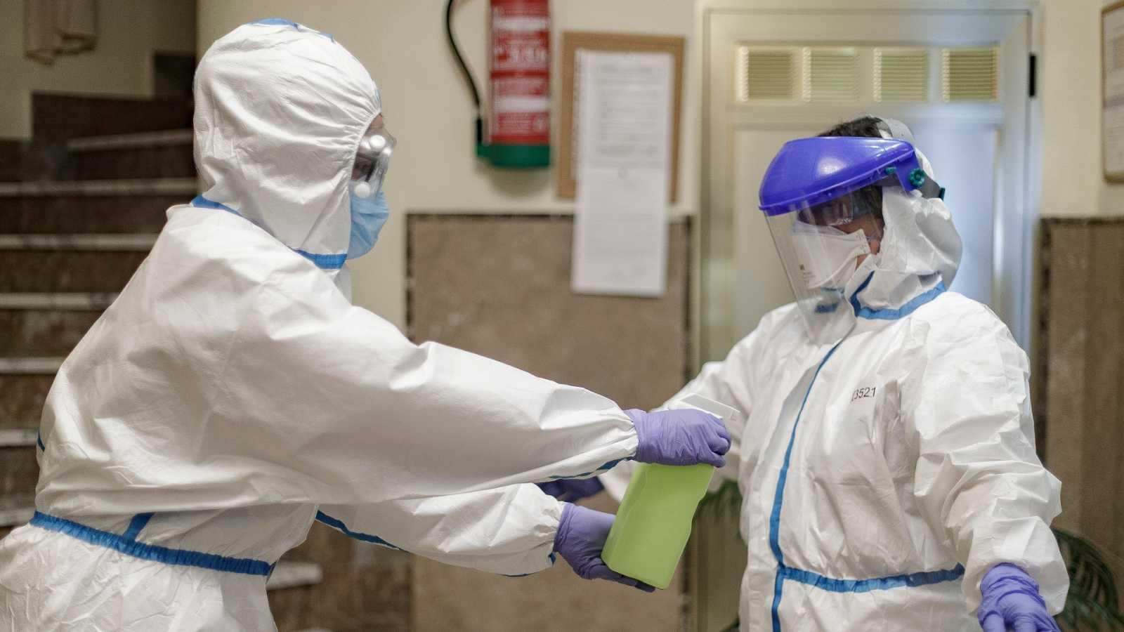 Una trabajadora desinfecta a un médico en el interior de una residencia de mayores.