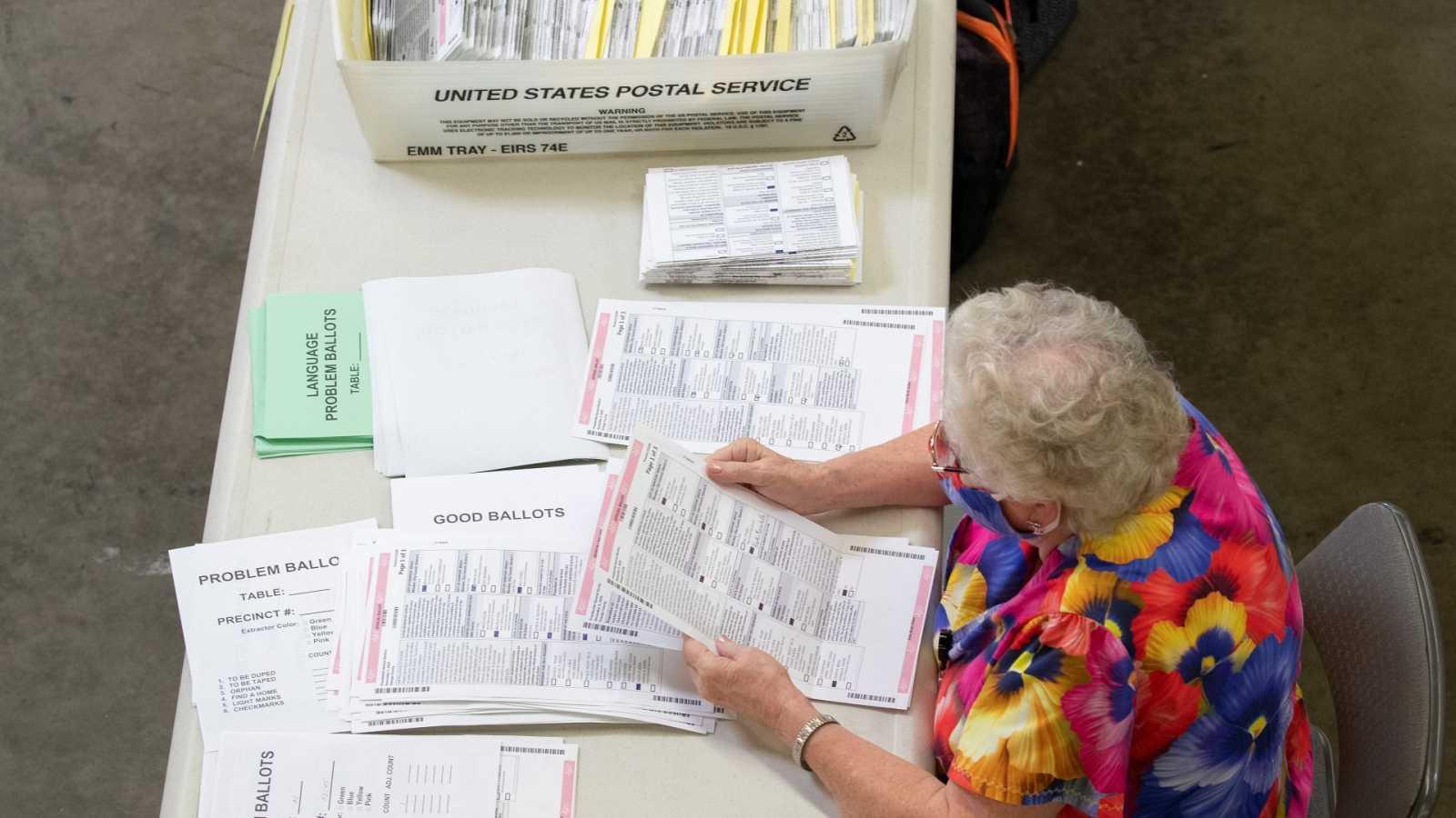 Una trabajadora electoral revisa papeletas de voto por correo en Santa Ana, California.