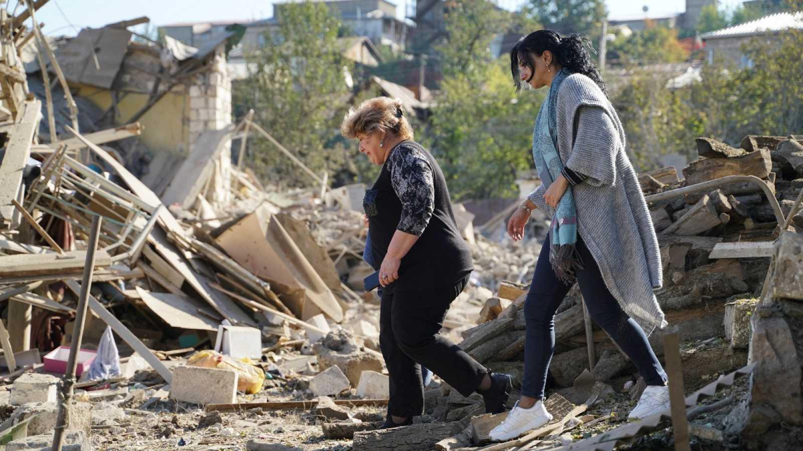 Dos mujeres caminan sobre los destrozos causados por las explosiones en Stepanakert (Nagorno Karabaj)