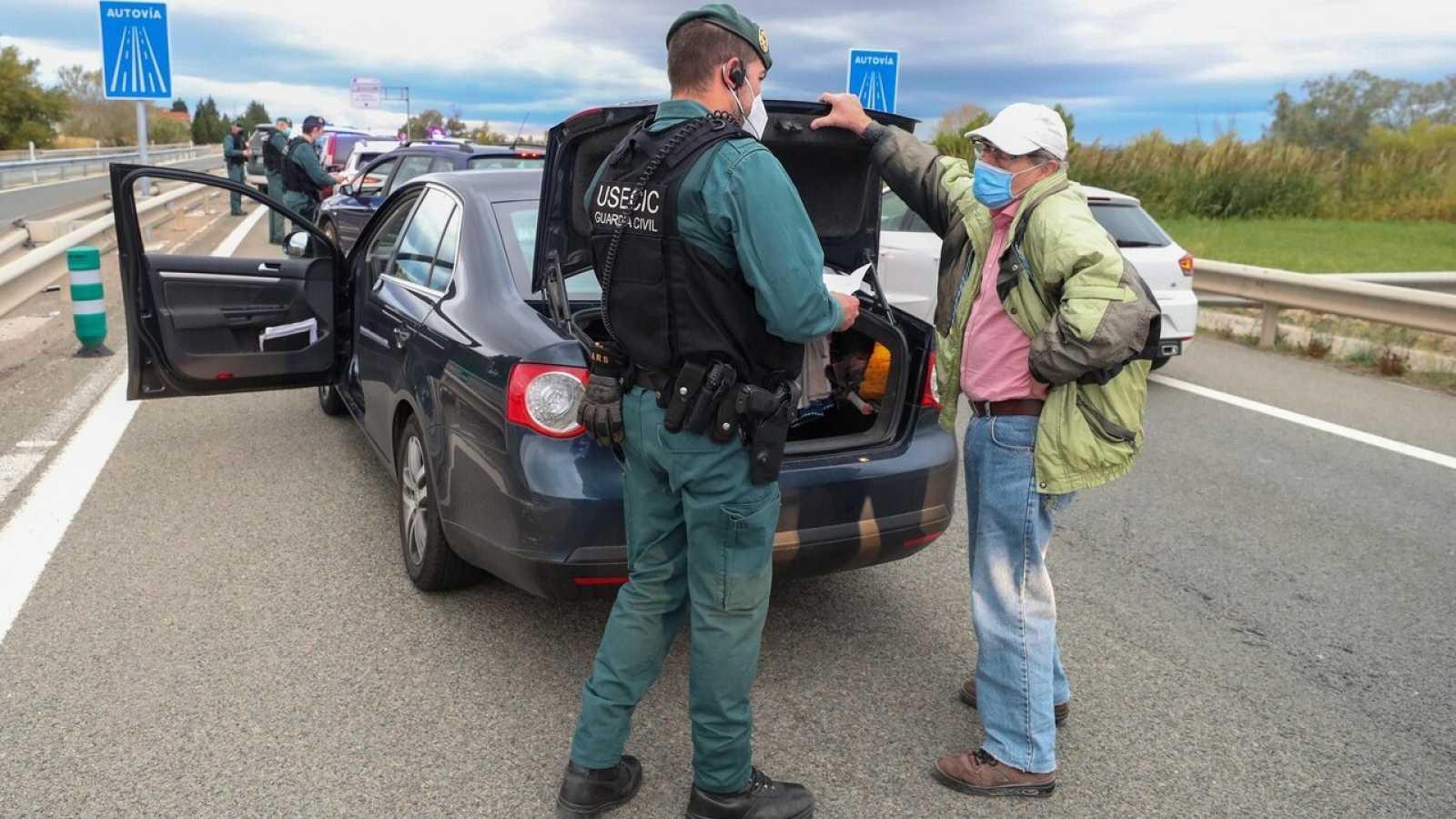 Agentes de la Guardia Civil controlan una carretera de acceso a Zaragoza para garantizar el cumplimiento del confinamiento perimetral de la capital aragonesa. EFE/Javier Cebollada