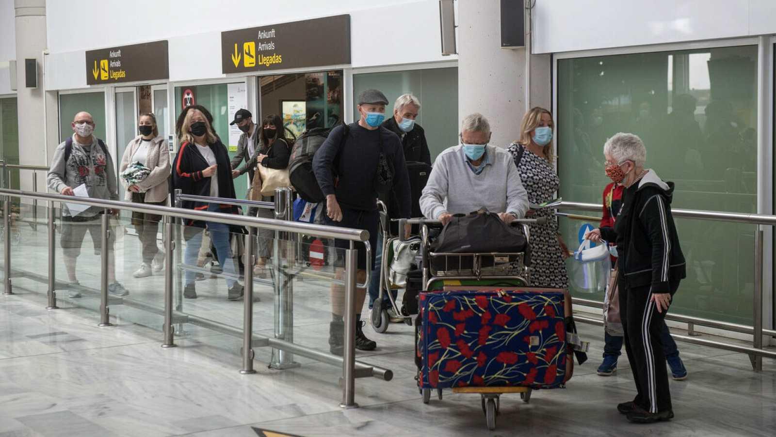 Varios turistas salen de la sala de recogida de equipajes a su llegada al aeropuerto César Manrique de Lanzarote, Canarias.