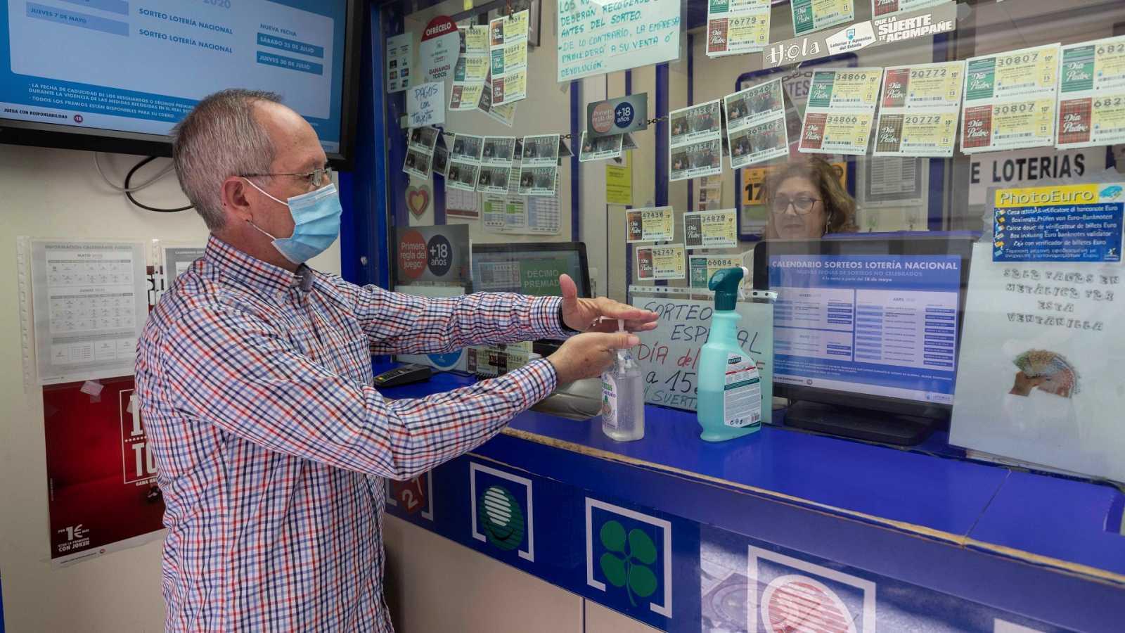 Un hombre se lava las manos con gel hidroalchólico antes de comprar lotería en una foto de archivo
