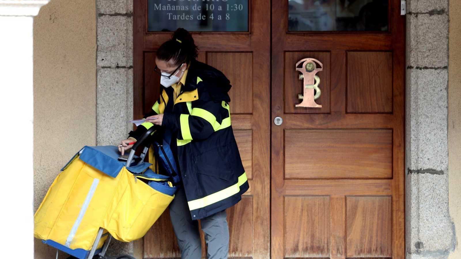 Una trabajadora de Correos entrega unas cartas en Ponferrada