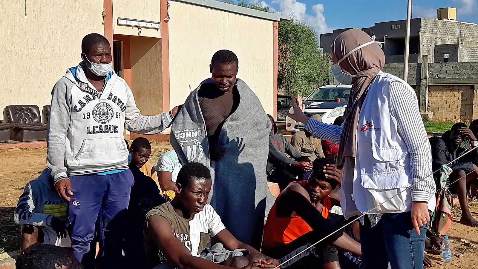 Los migrantes, que sobrevivieron a un naufragio mortal, se reúnen en una playa de arena en la costa de al-Khums, una ciudad portuaria a 120 kilómetros (75 millas) al oeste de la capital libia, Trípoli