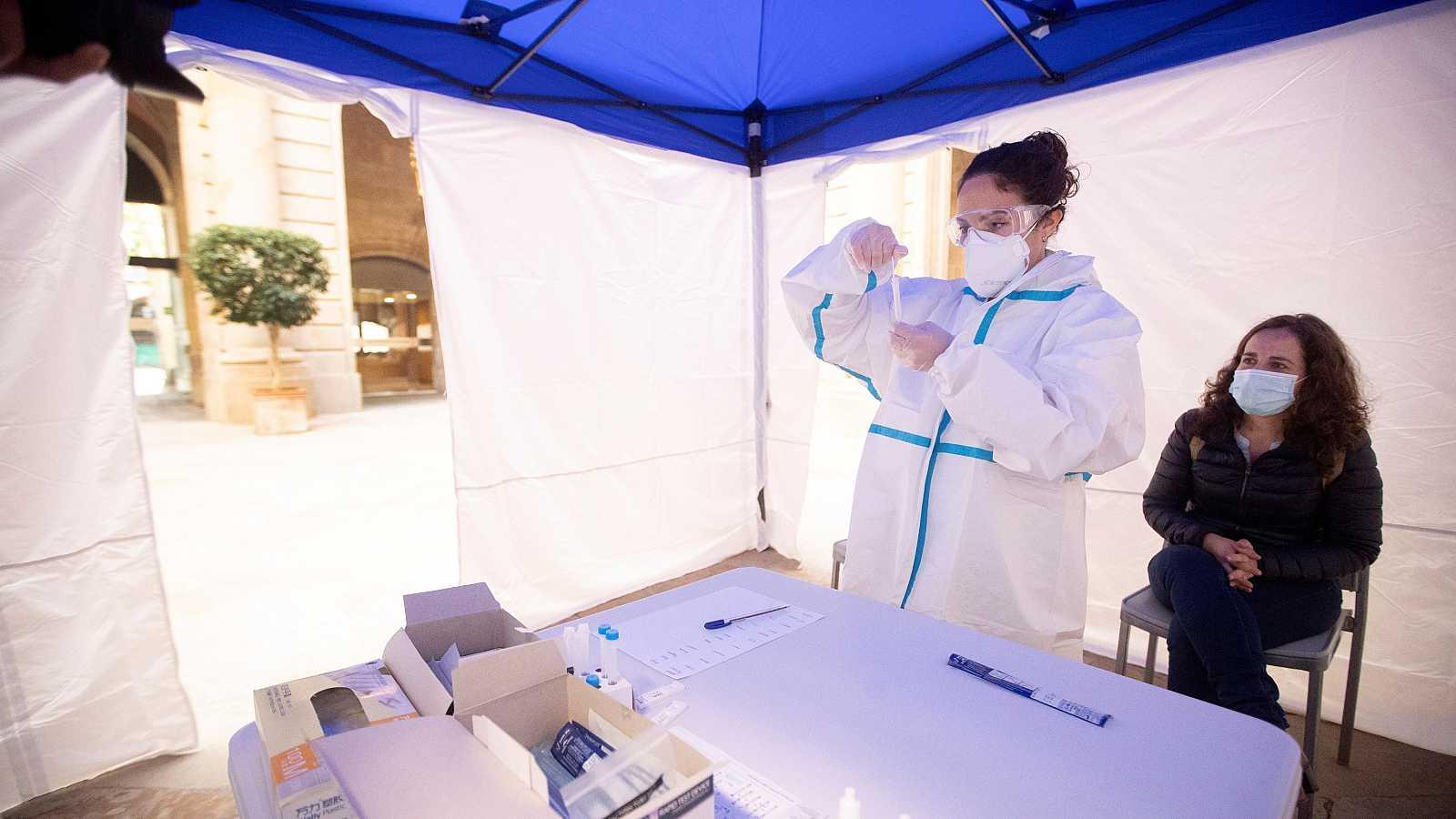 Una mujer se realiza una PCR en uno de los puntos habilitados por la Cambra de Comerç de Barcelona para realizar test rápidos de antígenos.
