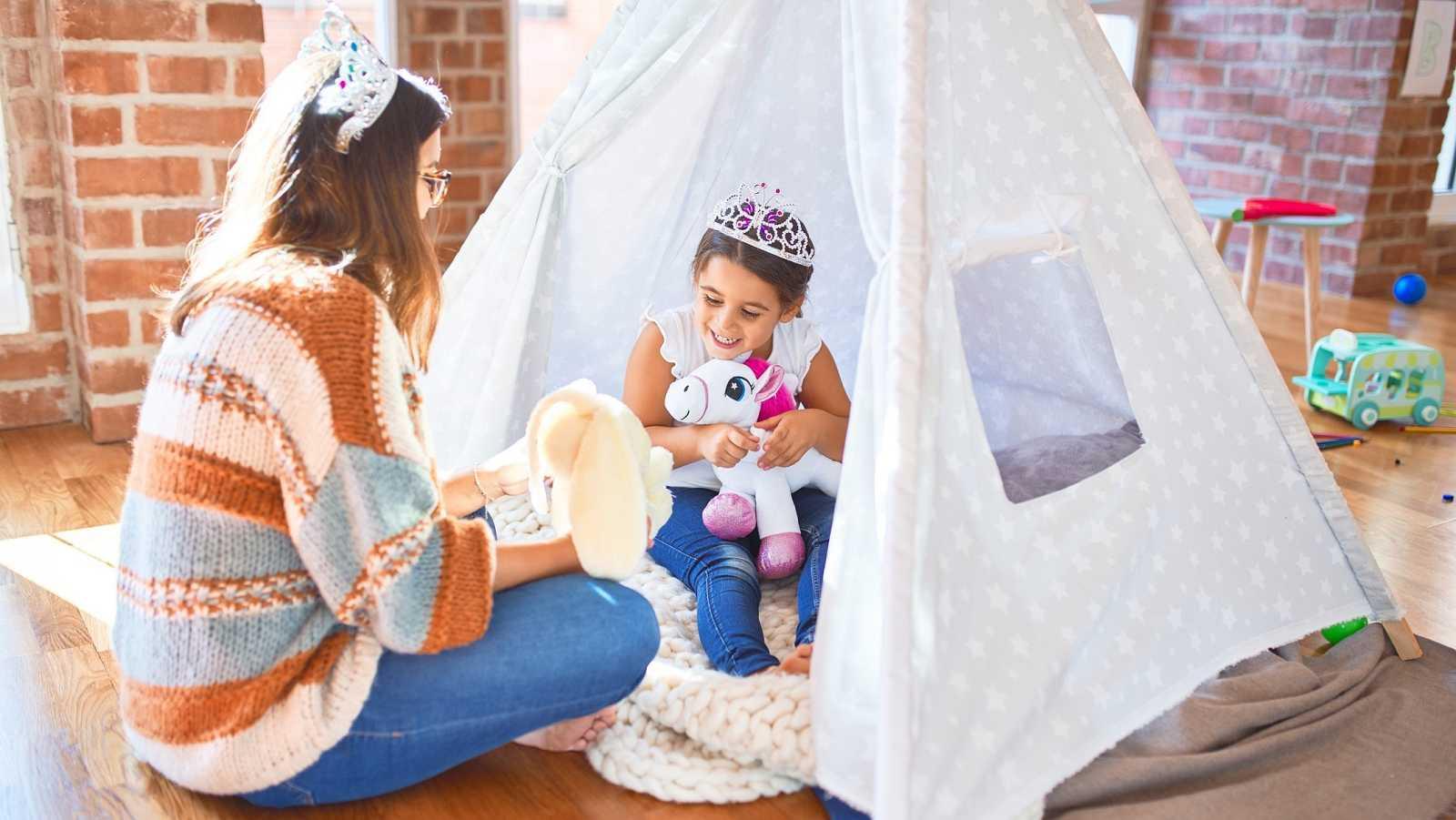 Una madre y su hija juegan en una tienda de campaña