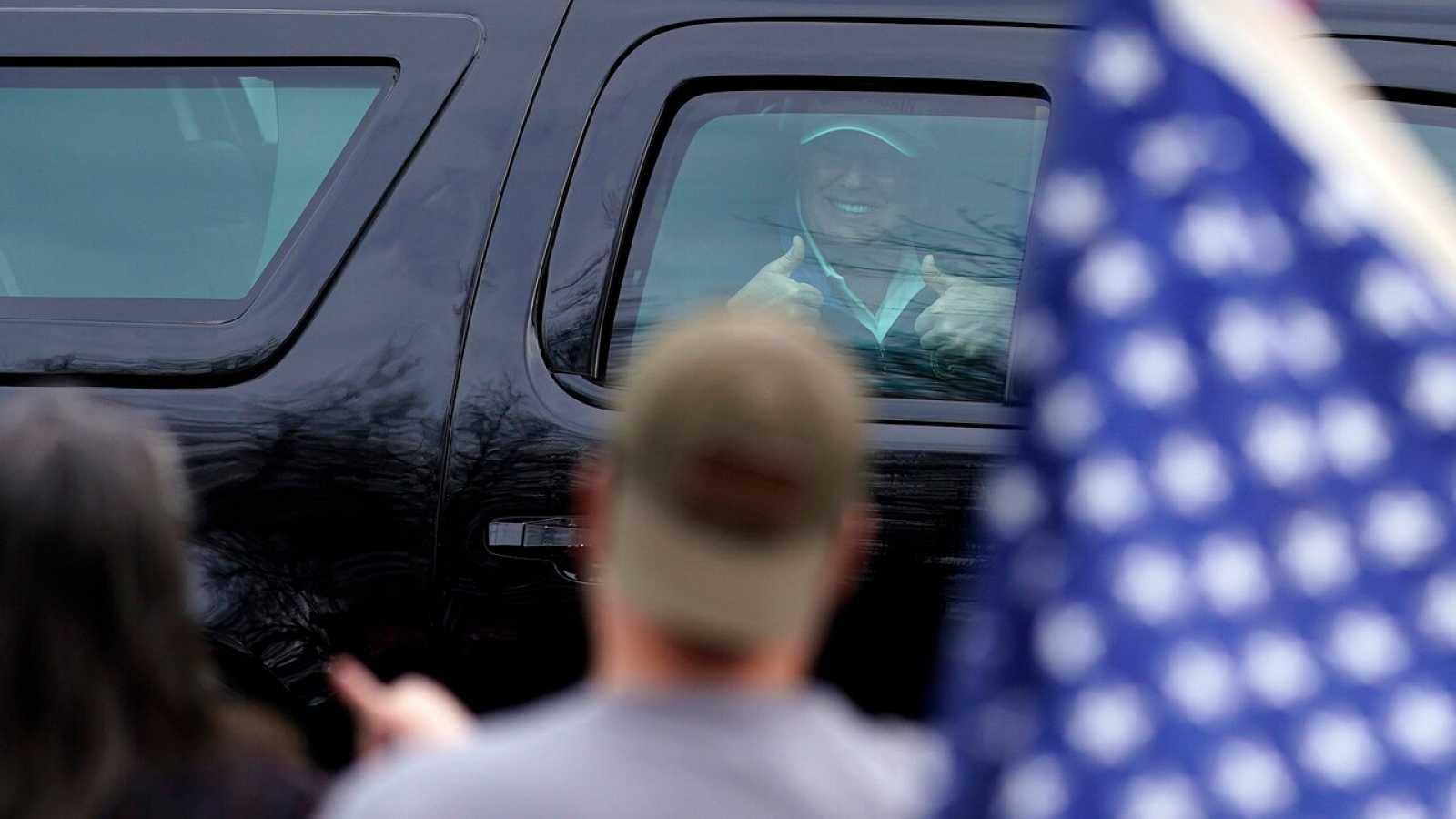 Trump saluda a sus seguidores desde el coche tras terminar de jugar al golf