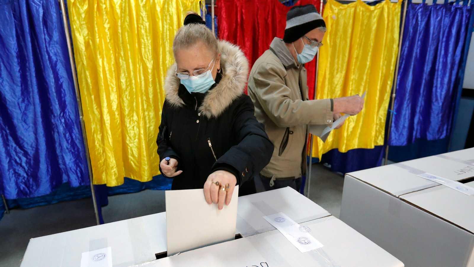 Una pareja votando en un colegio electoral de Bucarest