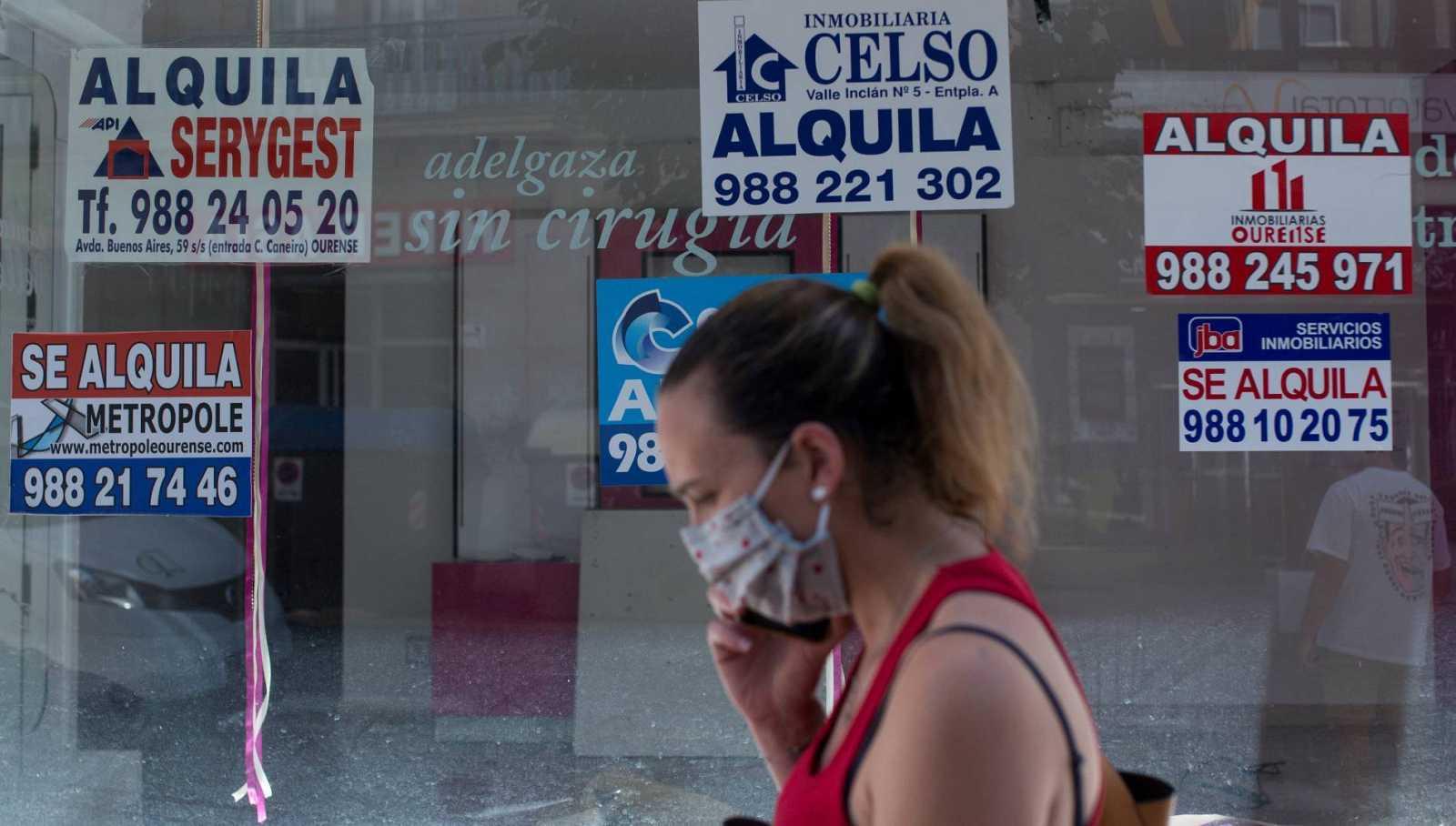 Una mujer con mascarilla pasa ante un comercio cerrado con varios carteles que anuncian su alquiler.