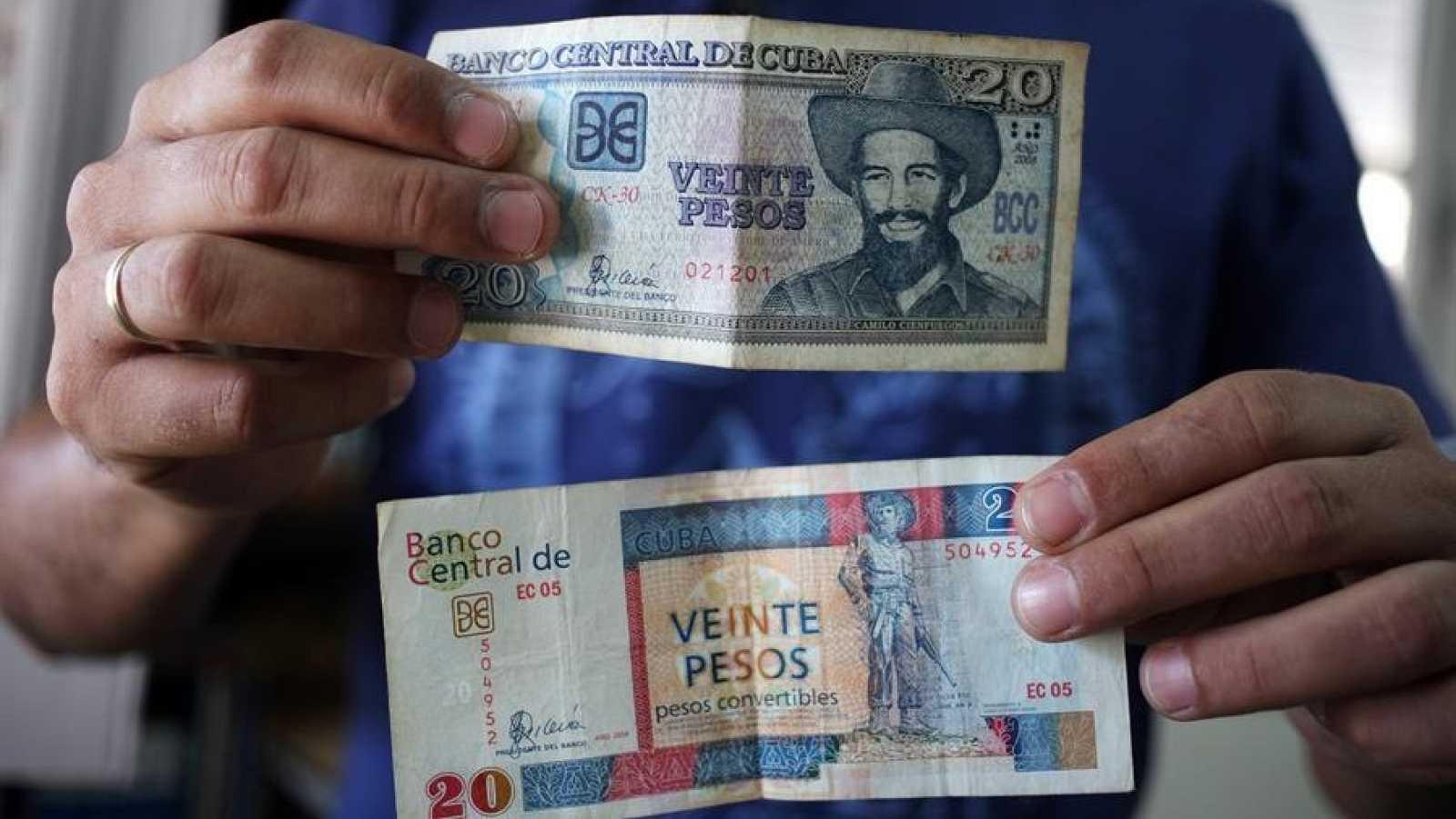 Un hombre muestra billetes cubanos de veinte pesos, uno de CUP (arriba) y otro de CUC (abajo)