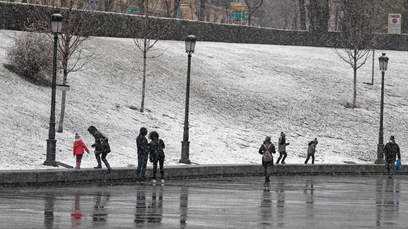 Varias personas ven caer la nieve a las puertas del Museo del Prado, en Madrid capital