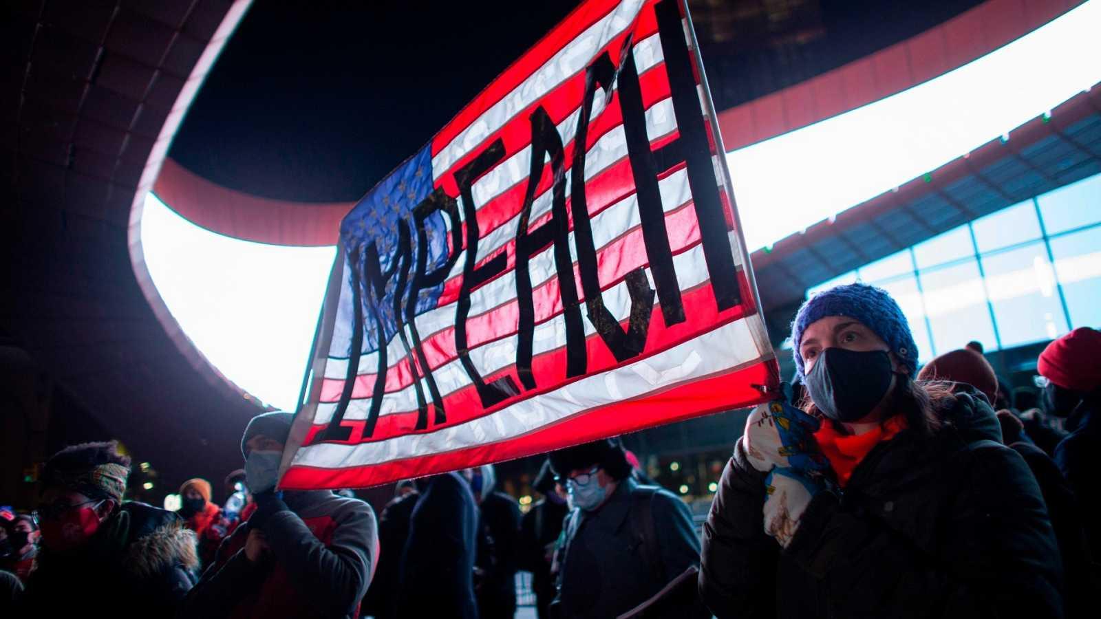 Manifestantes con una pancarta a favor del juicio político a Donald Trump