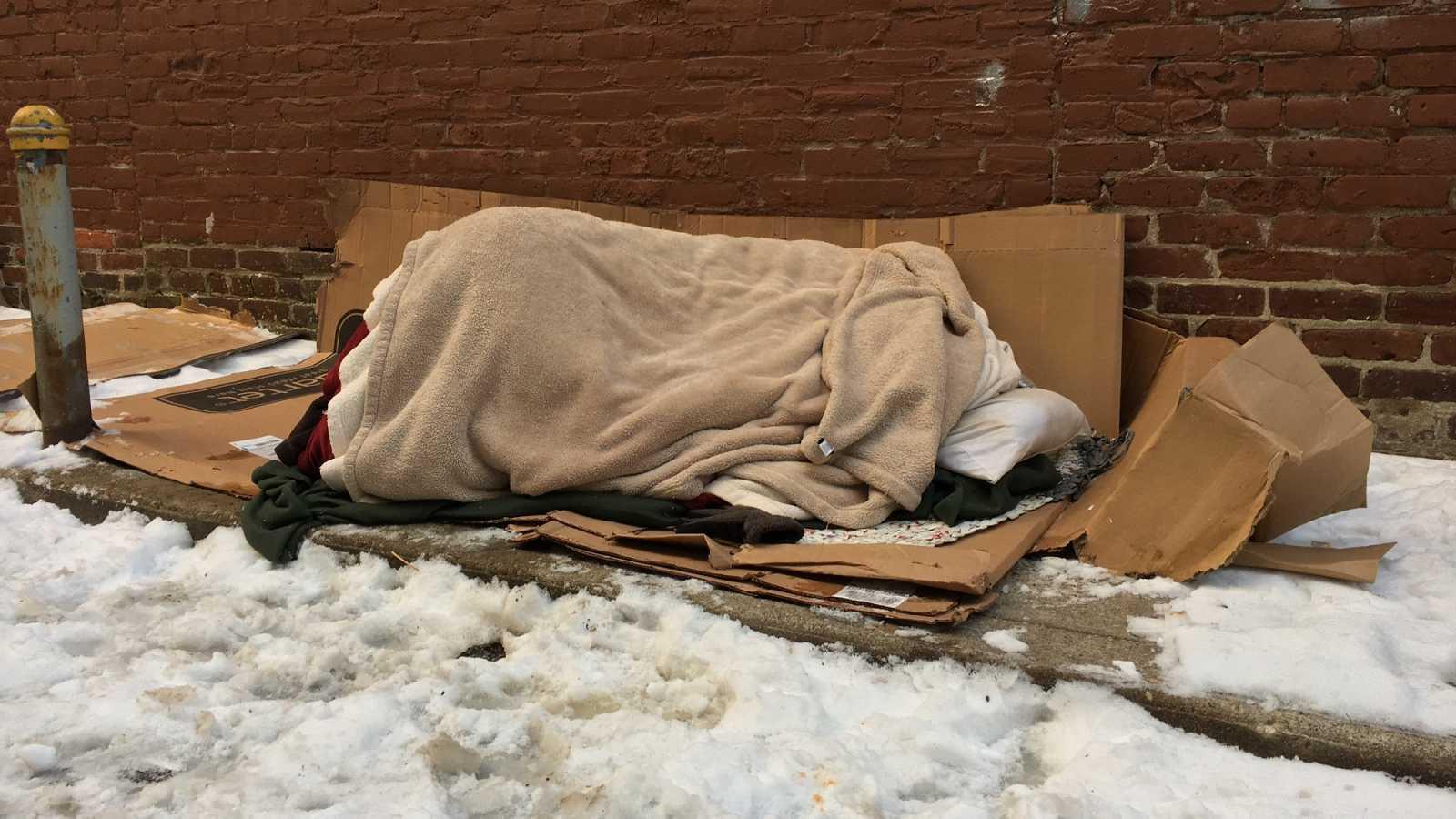 Una persona sin hogar durmiendo en la calle rodeada de nieve.