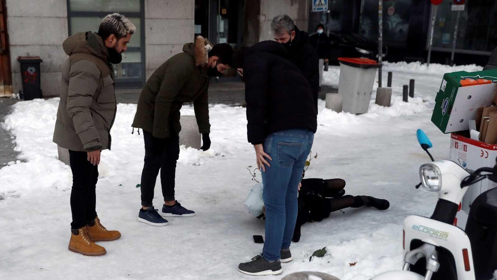 Varias personas asisten a una persona que ha sufrido una caída por el hielo sobre la calzada en Madrid, este miércoles.