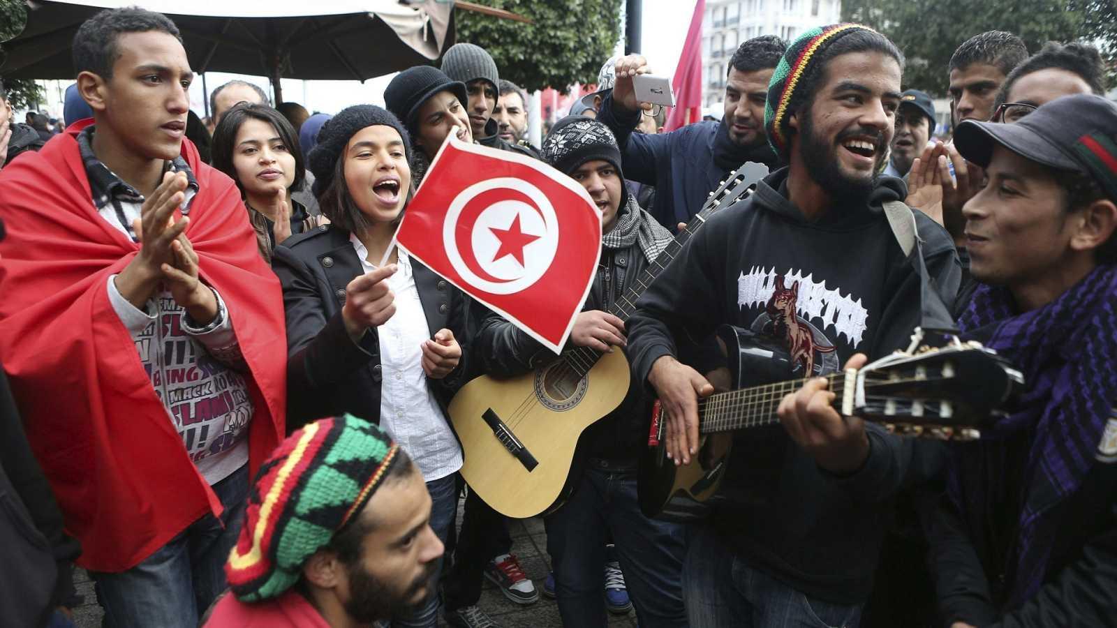 Jóvenes tunecinos cantan durante una manifestación