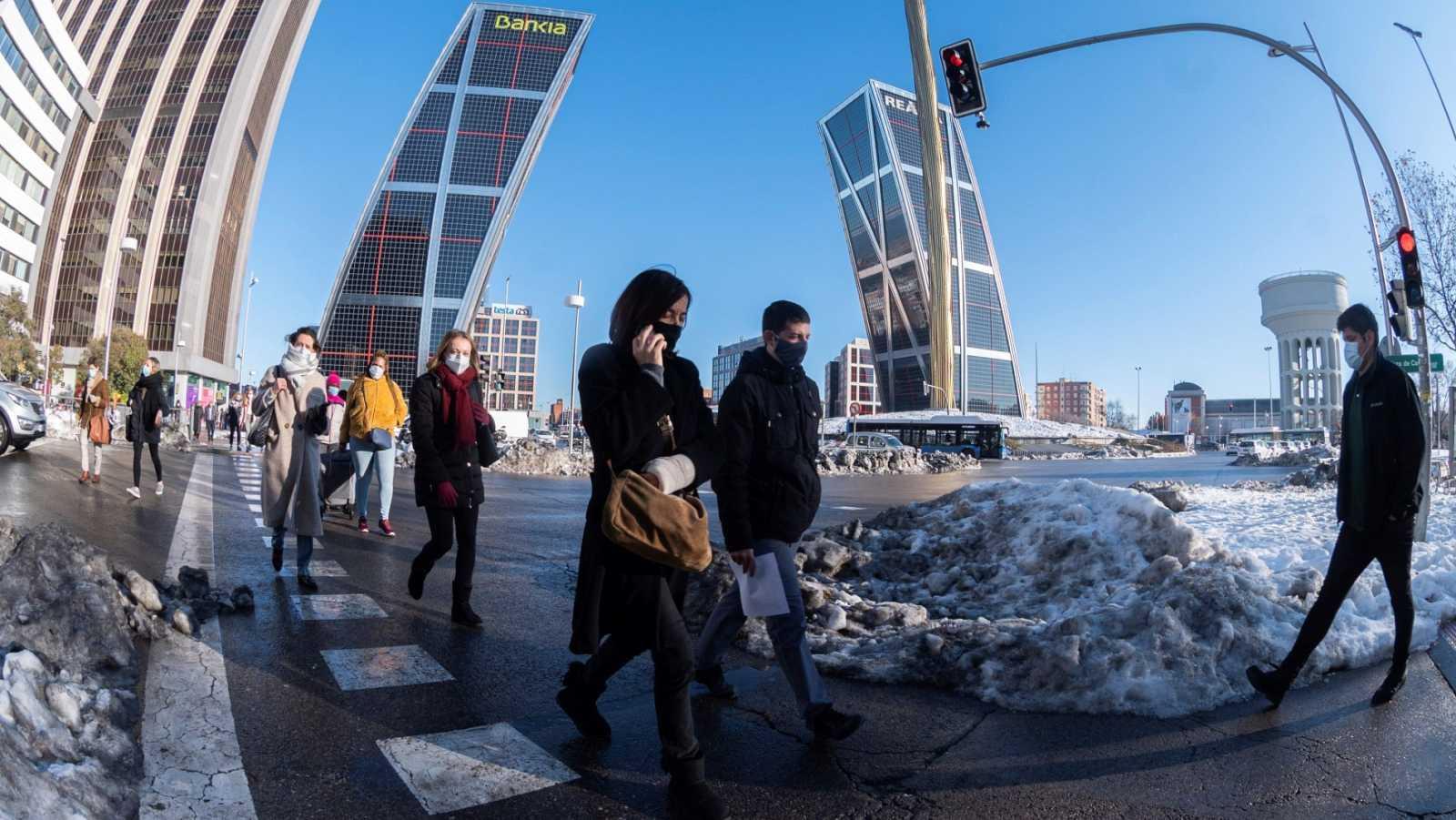 Peatones cruzan una calle en Plaza de Castilla en Madrid, este martes 19 de enero, once días después de le nevada que ha dejado el temporal Filomena