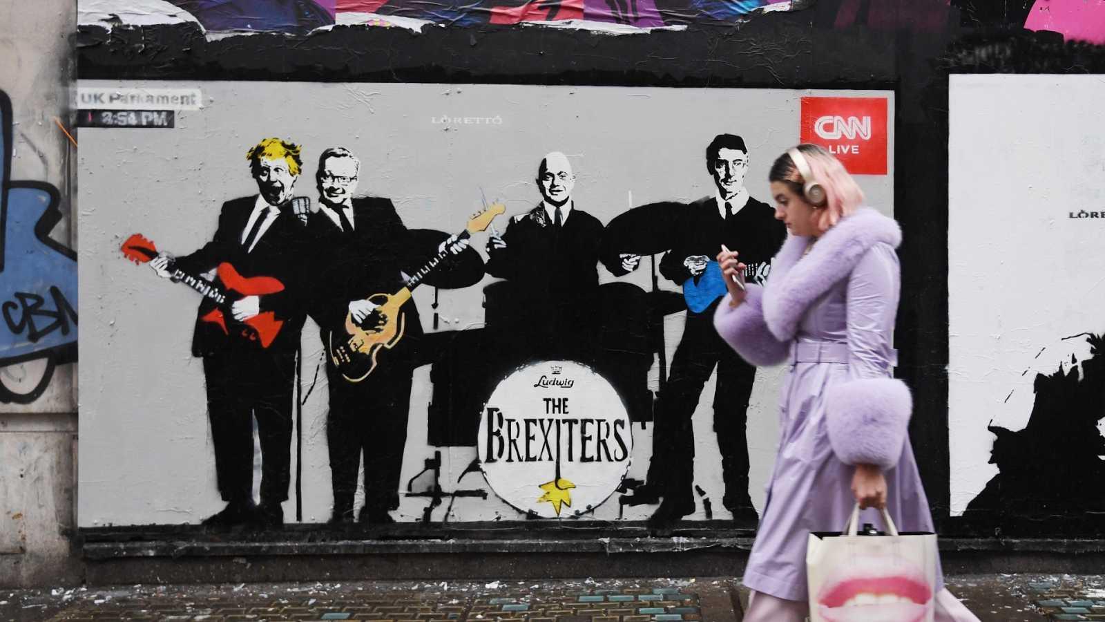 Una mujer camina frente a una obra de arte callejero del artista 'Loretto' en Londres, Reino Unido.