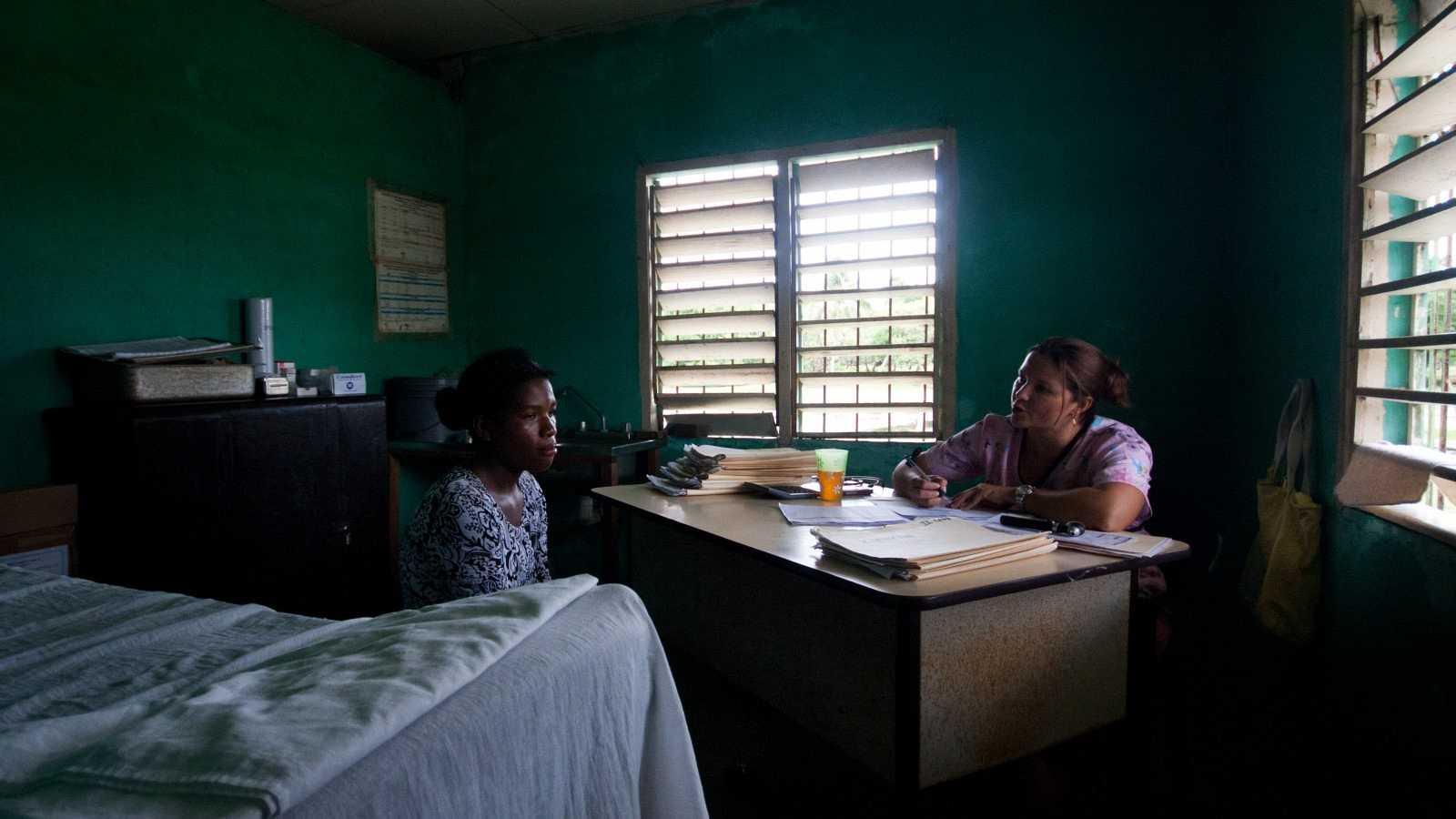 Una mujer habla con su doctora en una clínica rural en Honduras