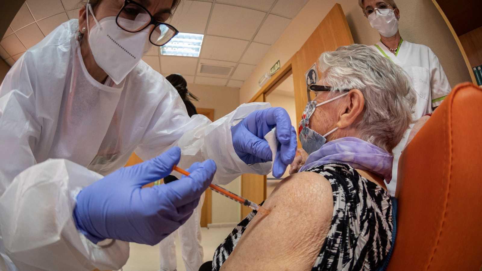Una usuaria de una residencia de ancianos de Alcalá de Henares (Madrid) recibe una dosis de la vacuna contra el covid.