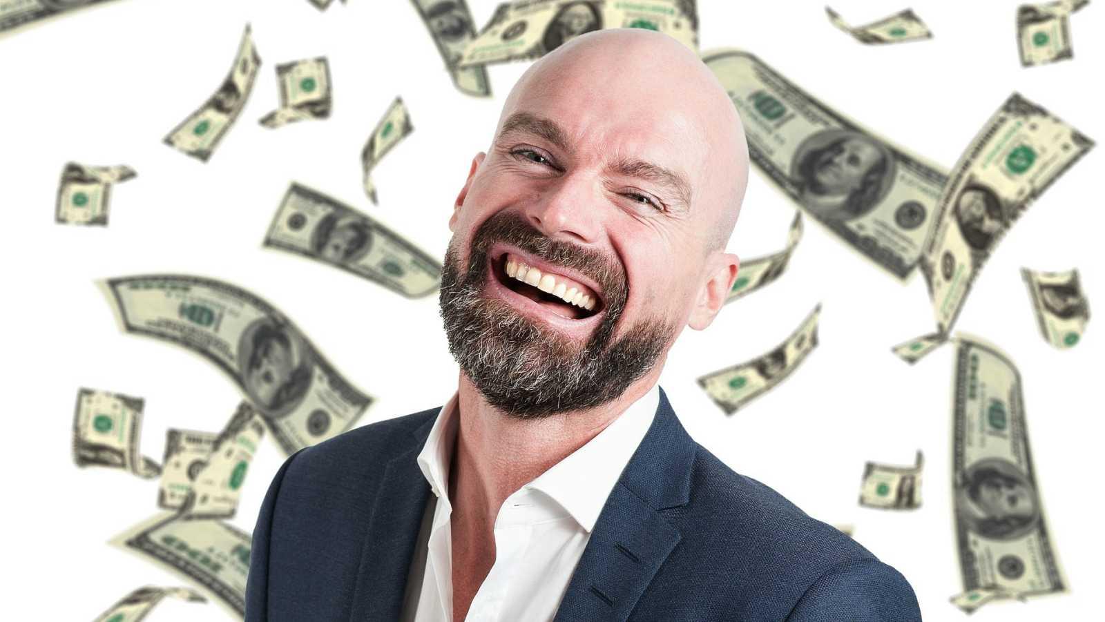 Un hombre feliz la haber ganado la lotería con billetes cayendo desde el cielo