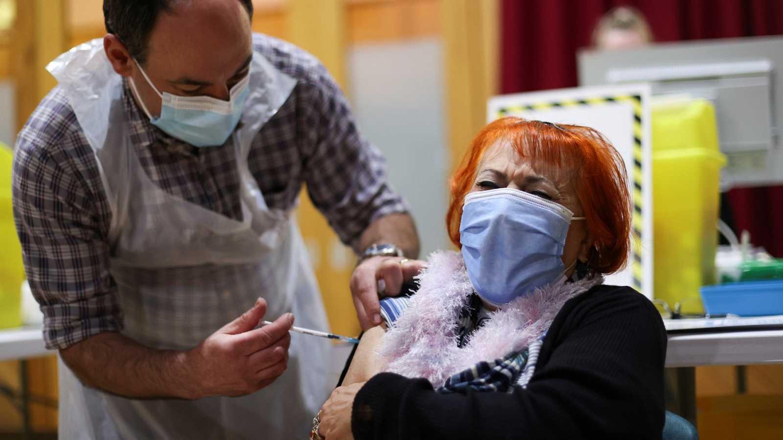 Una mujer recibe una vacuna contra la COVID-19 en Reino Unido