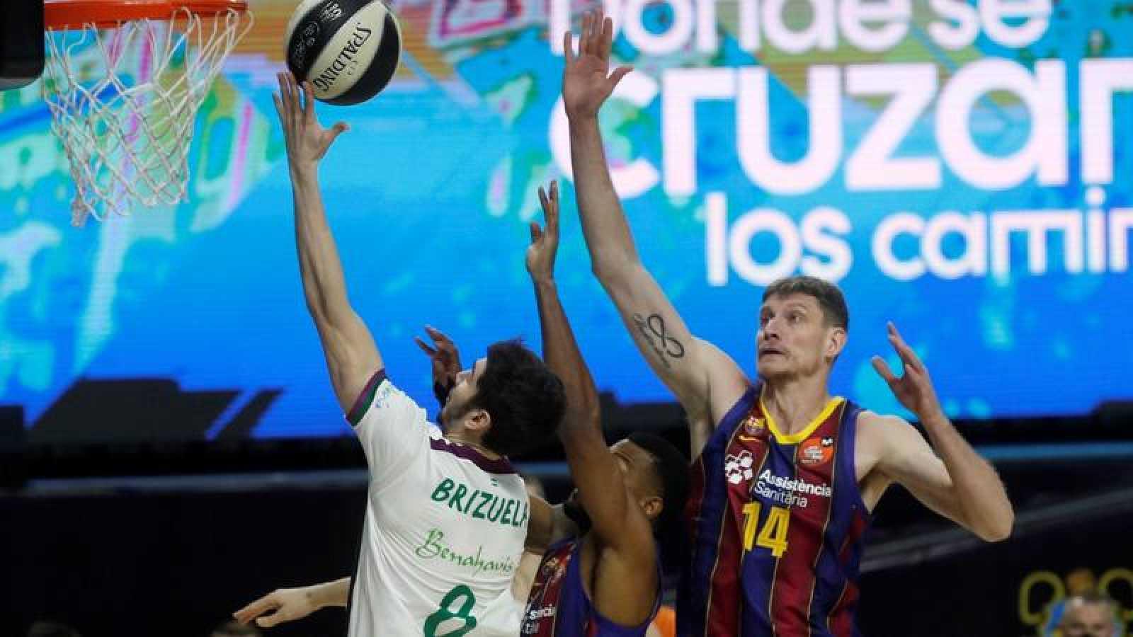 El base de Unicaja Darío Brizuela (i) entra a canasta defendido por Artem Pustovyi (d) y Cory Higgins (c), ambos del Barça.