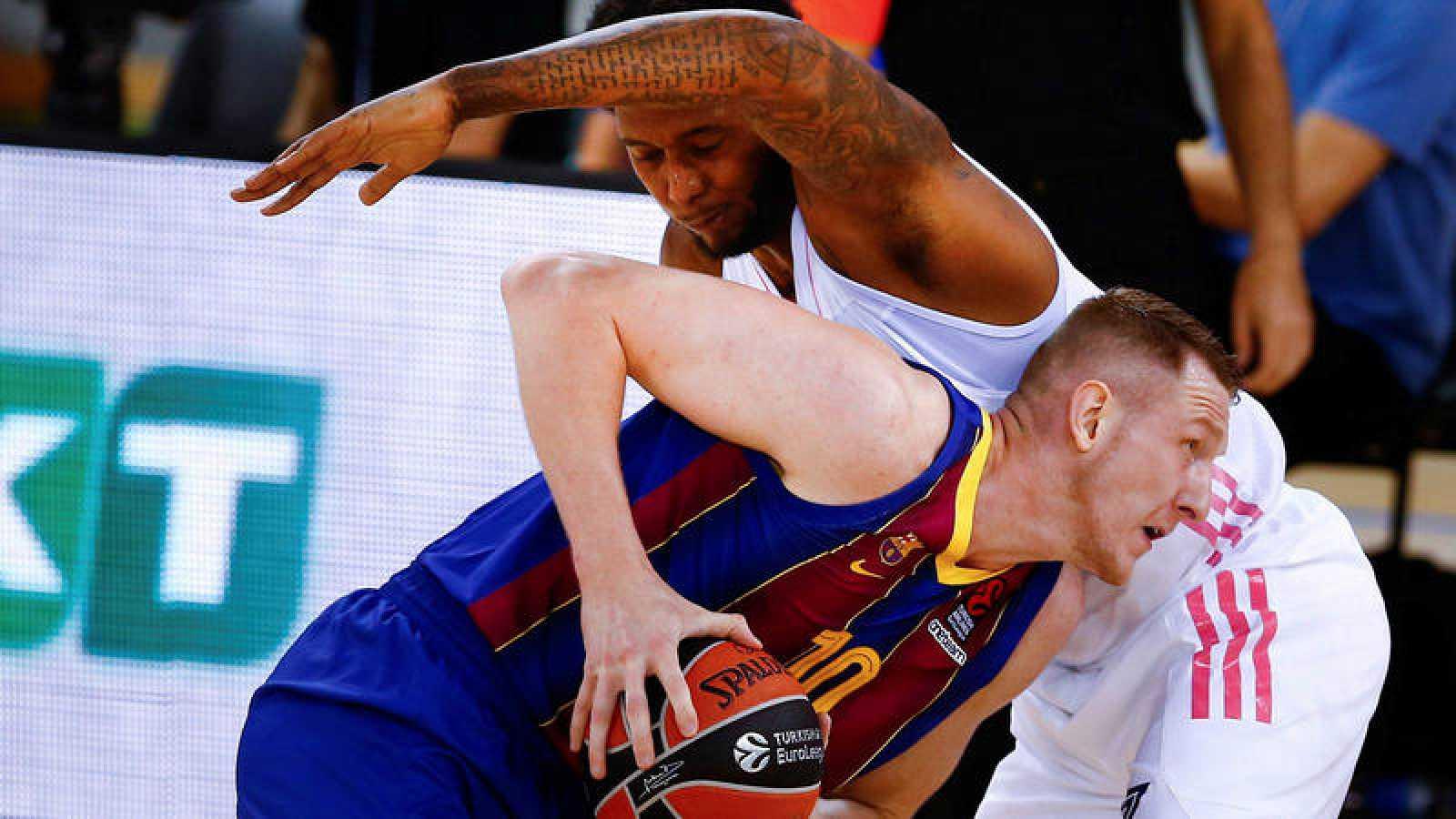El alero letón del Barça Rolands Smits lucha con Trey Thompkins, del Real Madrid.