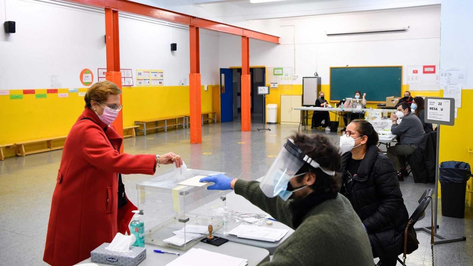Una mujer deposita su voto en un colegio de L'Hospitalet de Llobregat (Barcelona).