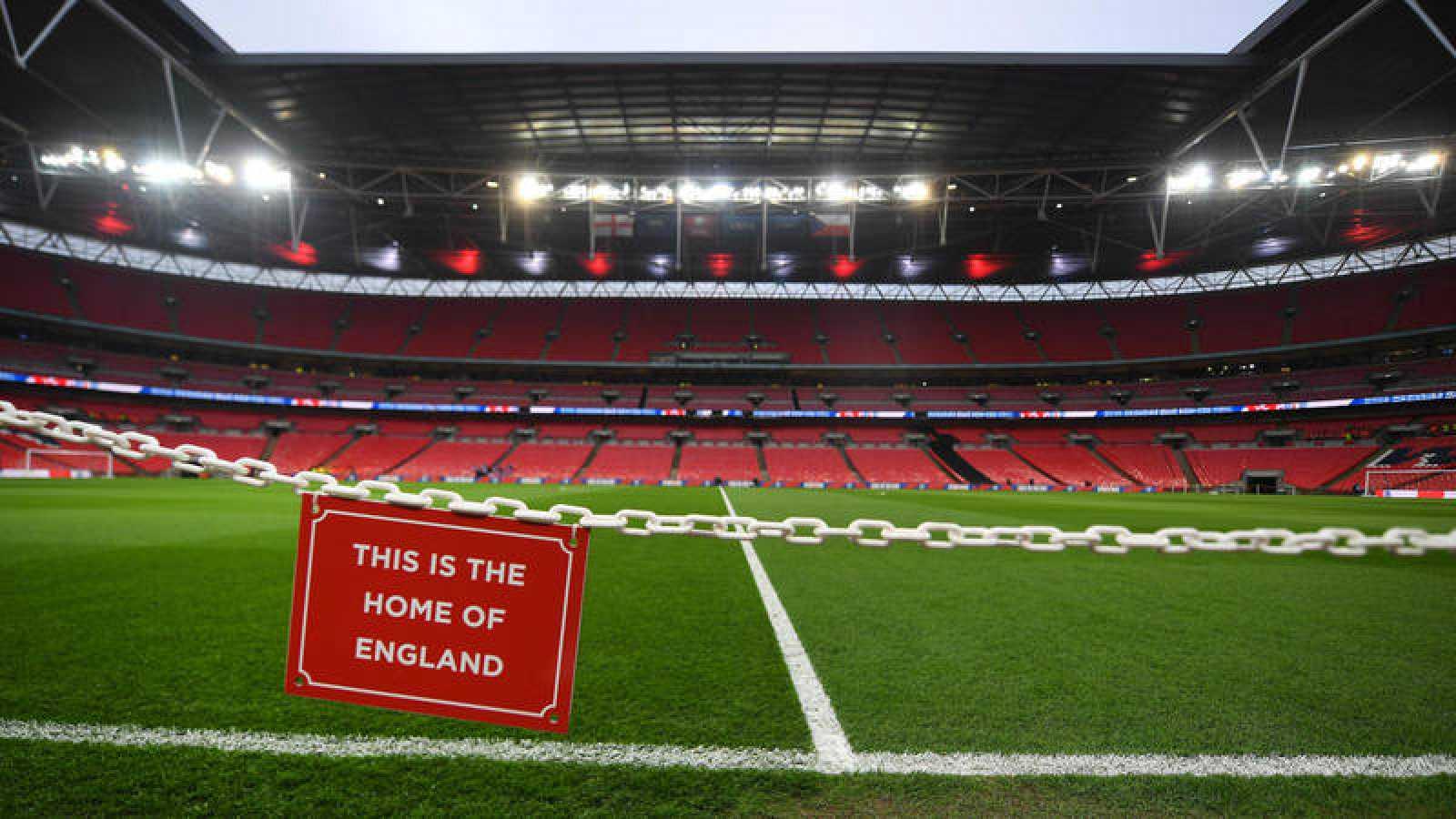 """Vista del estadio de Wembley vacío con un letrero en primer plano con la leyenda, en inglés """"Esta es la casa de Inglaterra"""""""