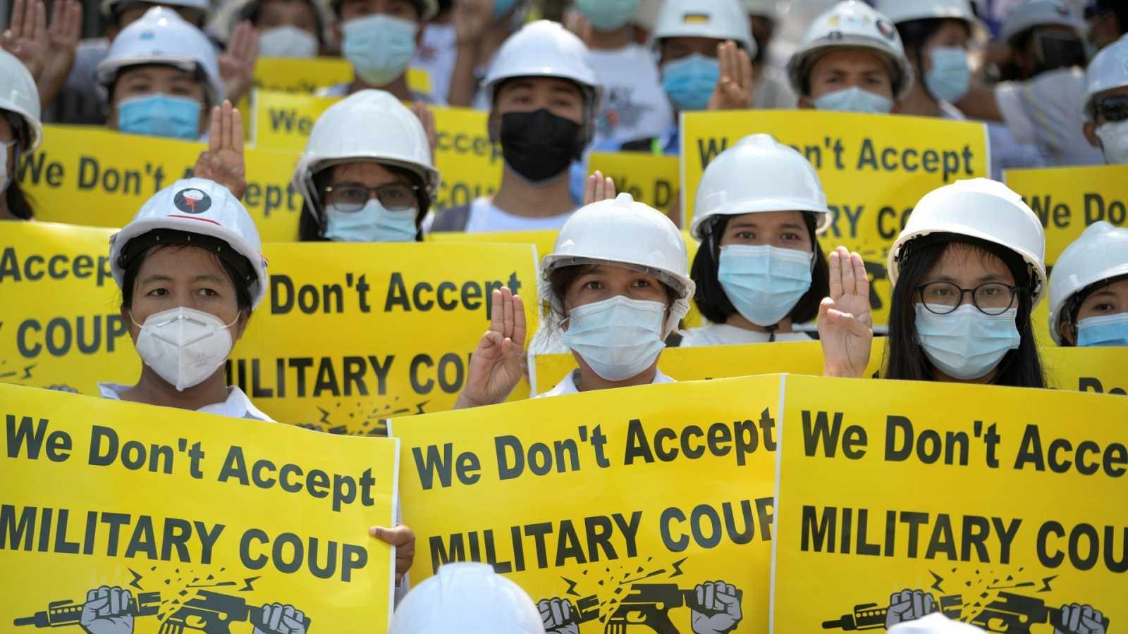 Varios manifestantes sujetan pancartas en una protesta contra el golpe de Estado en Birmania