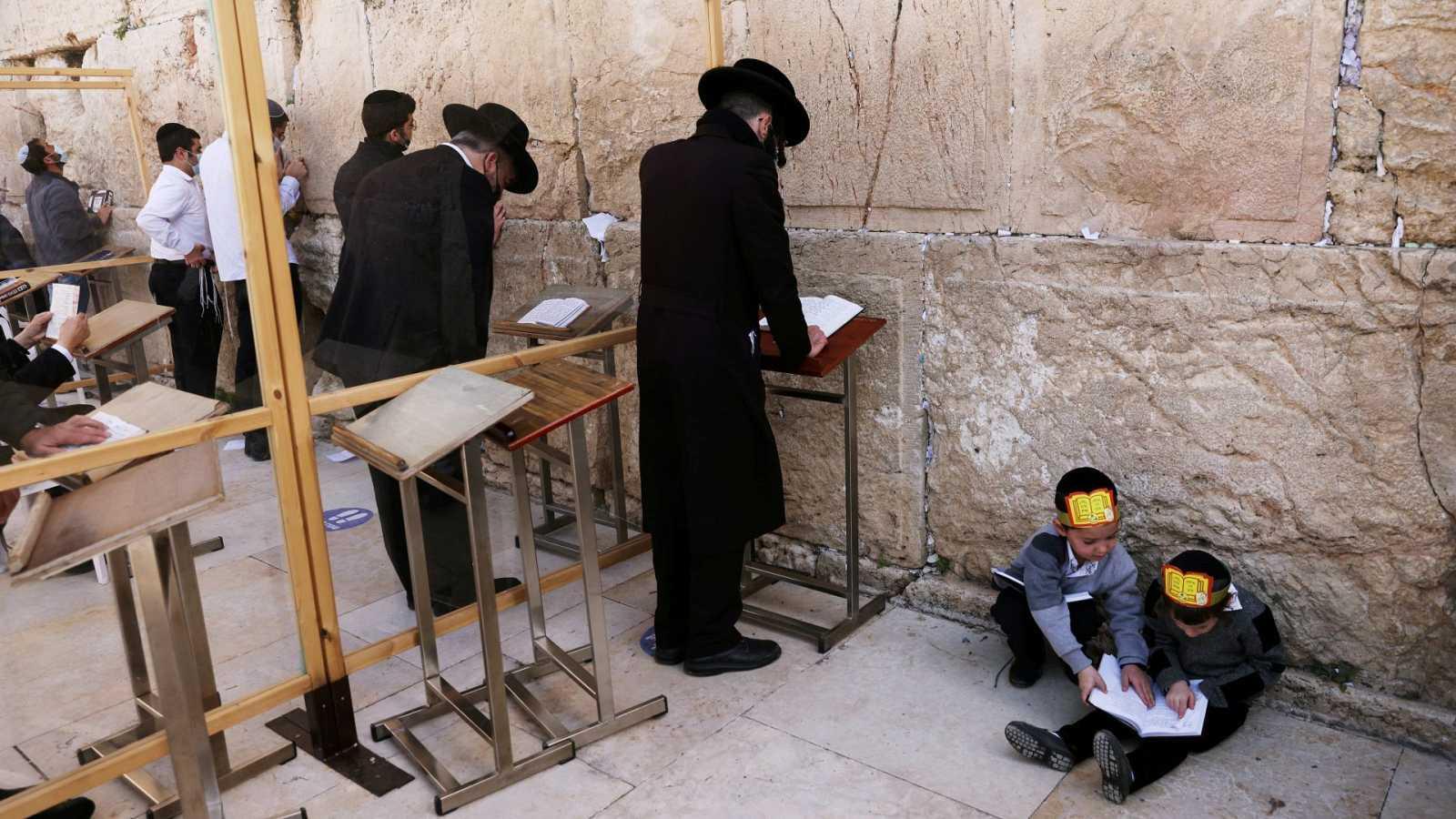 Niños judíos ultraortodoxos juegan mientras varios hombres rezan frente al Muro de las Lamentaciones de Jerusalén