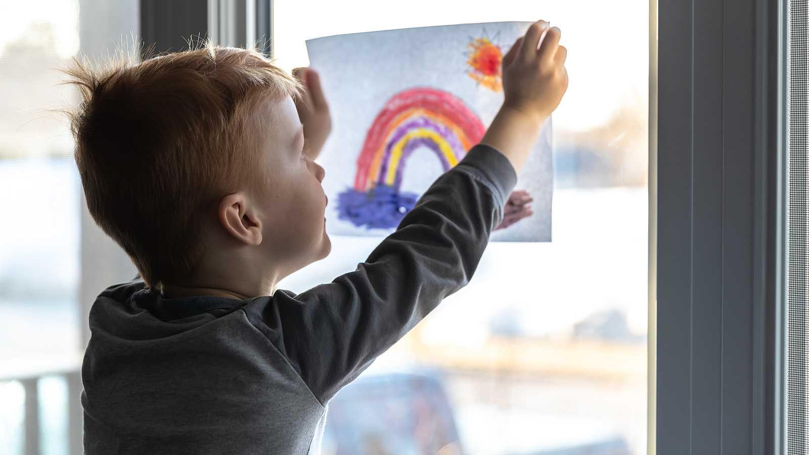 Un niño cuelga un dibujo con un arco iris durante el confinamiento domiciliario.