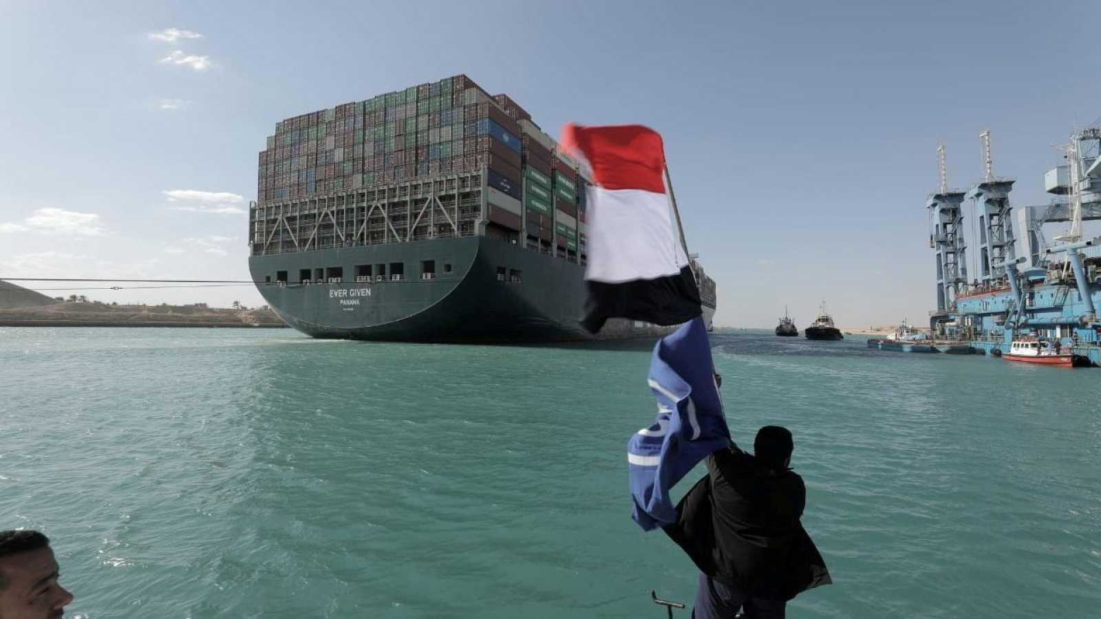Un hombre con una bandera egipcia después de que el Ever Given fuera reflotado