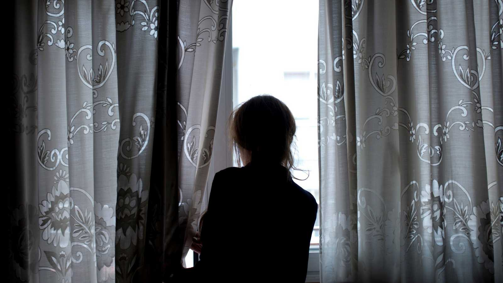 Una mujer observa a través de la ventana de su vivienda