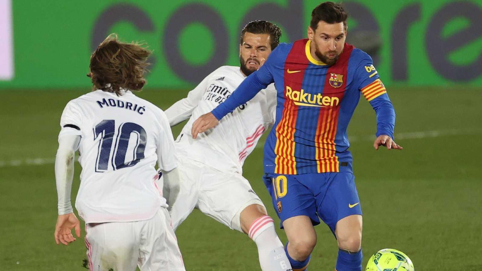 Leo Messi, que jugó su Clásico número 45, protege el balón ante Modric y Nacho.
