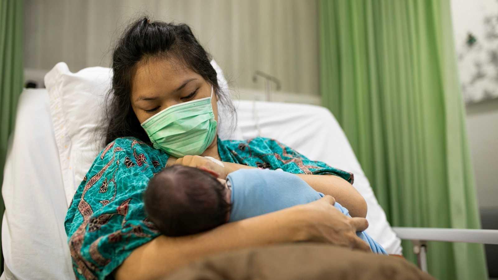 Una madre con mascarilla sostiene a su bebé recién nacido.