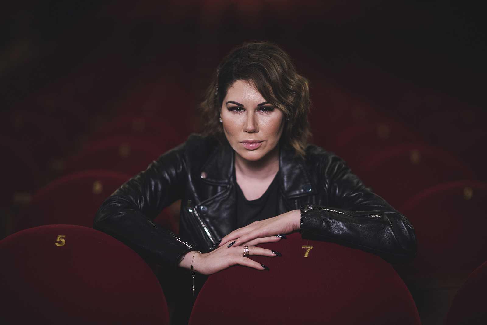 La cantante Tamara en un posado en 2019 vestida de cuero negro entre los asientos granates de un teatro