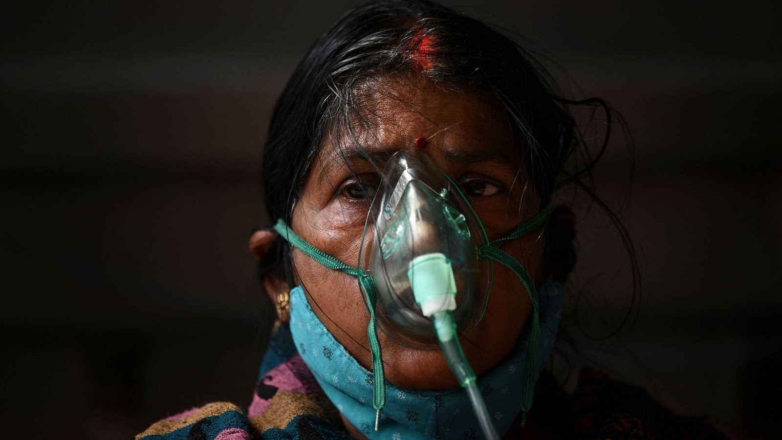 Una mujer respira con la ayuda de un respirador en una carpa instalada al borde de una carretera en Ghaziabad.