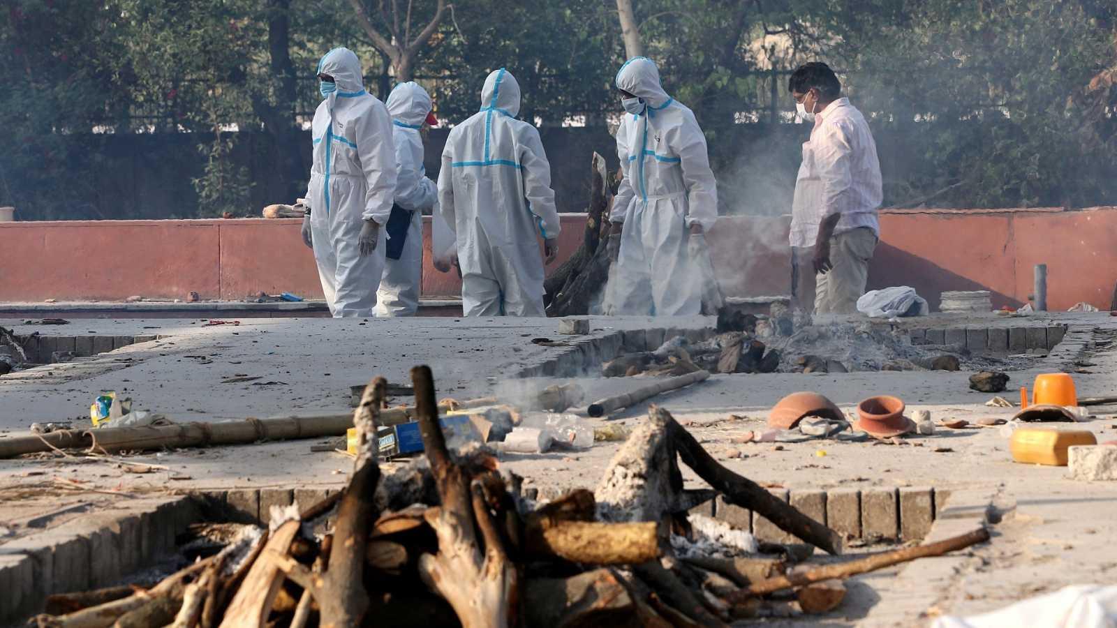Los miembros de una familia, con equipo de protección personal (EPI), realizan los últimos ritos para las víctimas de COVID-19 en un crematorio cerca de Nueva Delhi, India.