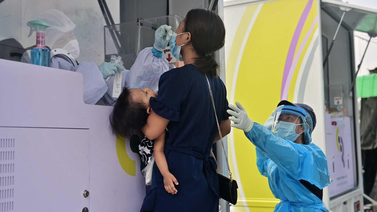 Un médico realiza una preba nasal a una mujer en Bon Kai una de las áreas con el mayor número de casos positivos de coronavirus