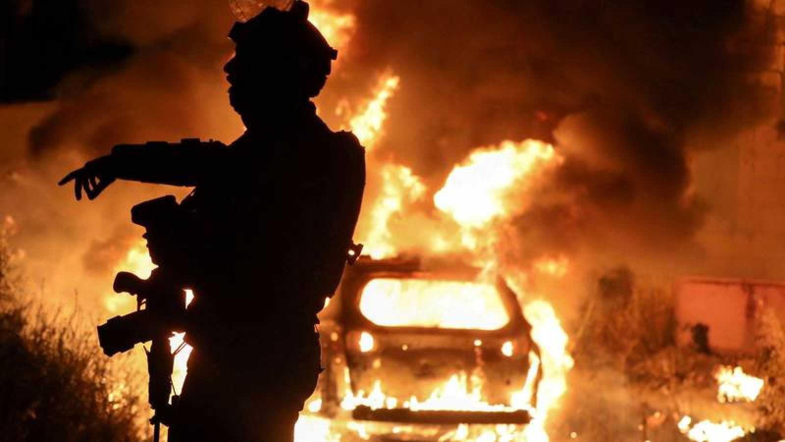 Un coche incendiado durante las protestas en la zona ocupada