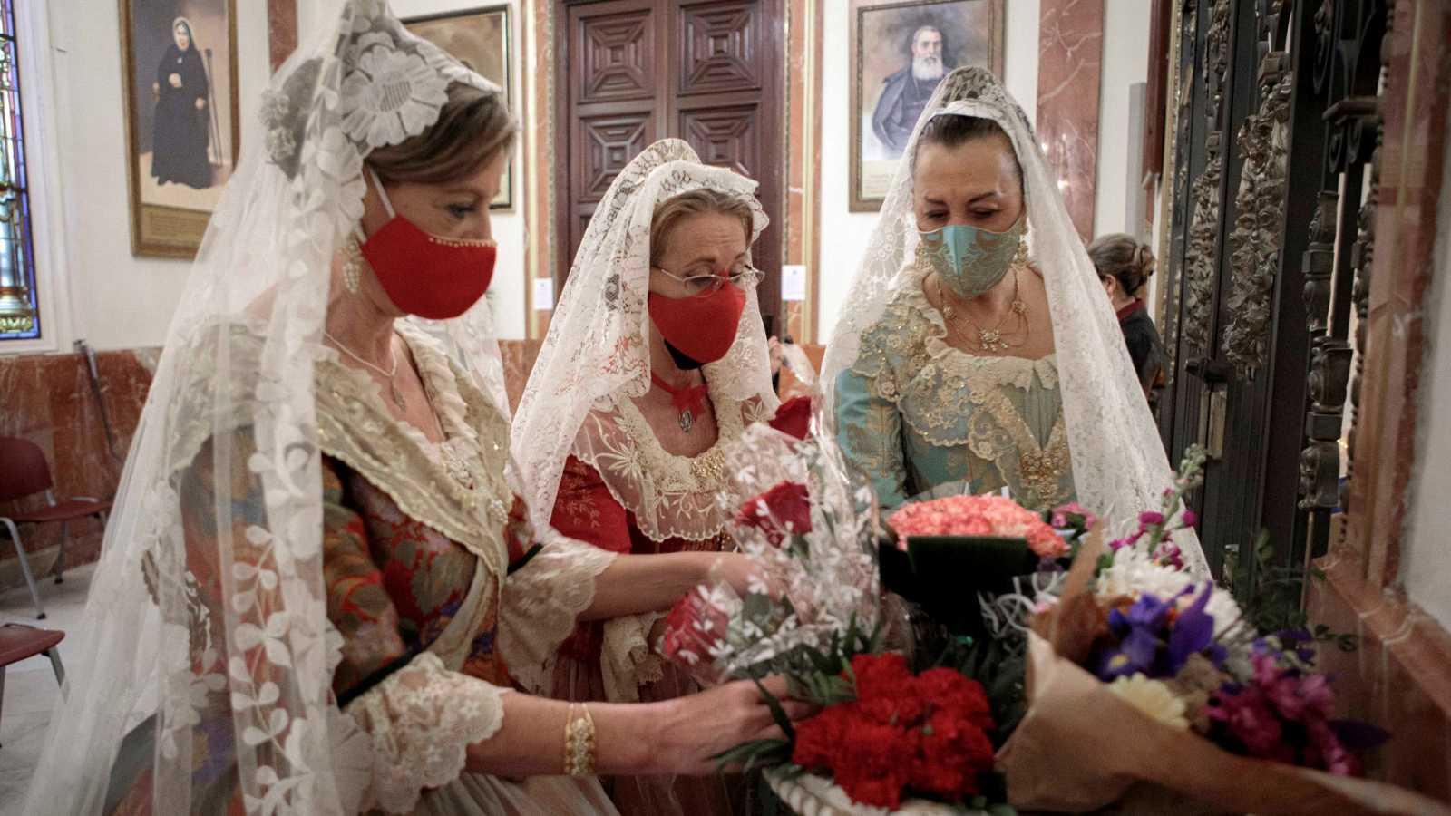 Varias mujeres con vestido de fallera realizan una ofrenda floral a la virgen de los Desamparados