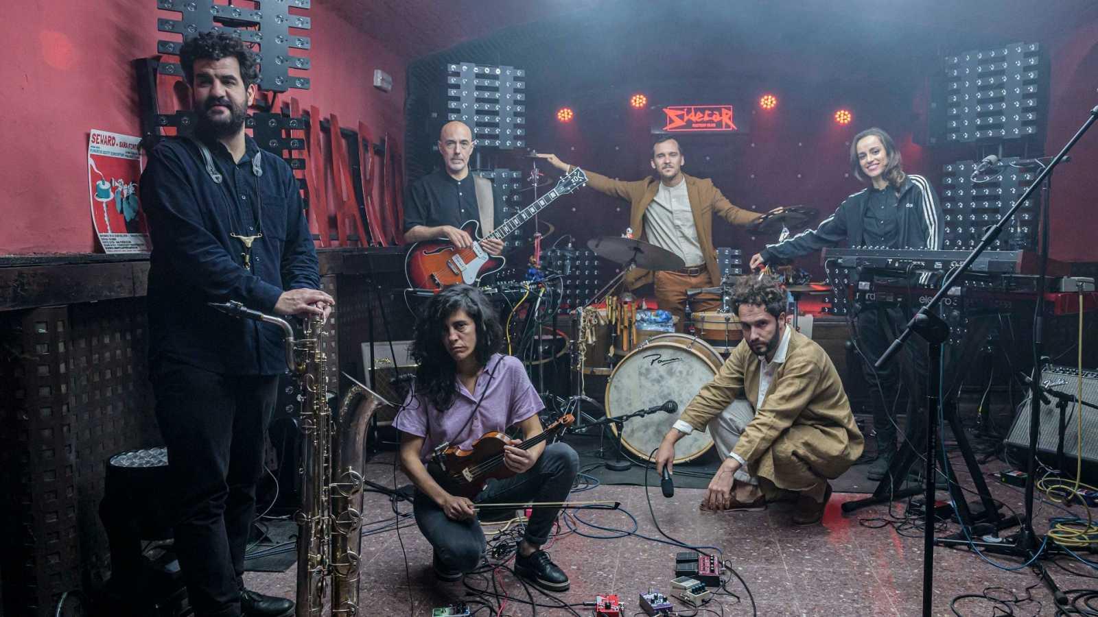 Foto de família del grup a l'escenari de la sala Sidecar